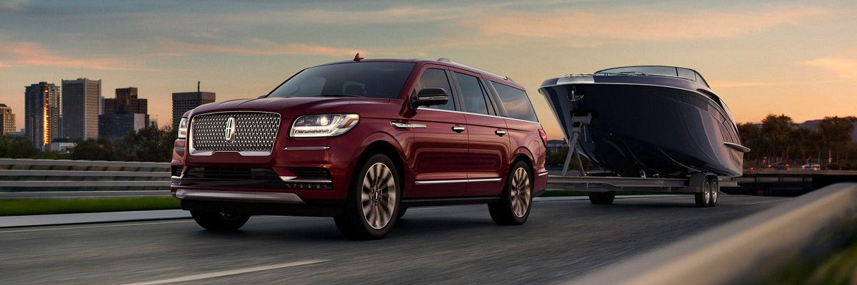 red 2018 Lincoln Navigator pulling a big boat in the highway